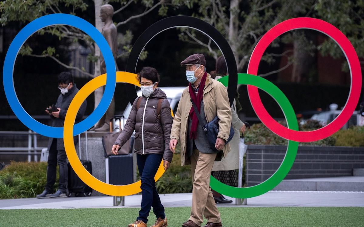 dos-japoneses-caminan-frente-logo-juegos-olimpicos-tokio-pleno-brote-coronavirus-1877893.jpg