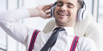 Smiling young man in suit is listening music in headphone in office.
