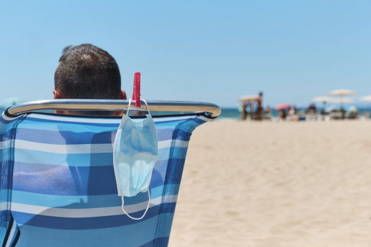 closeup of a caucasian man, sitting in a deck chair on the beach, seen from behind, and his surgical mask hanging from the chair, as he is taking a breather of wearing it or sunbathing