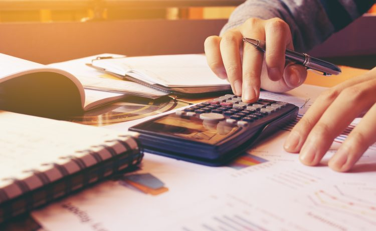 Woman using calculator with doing finance at home office.