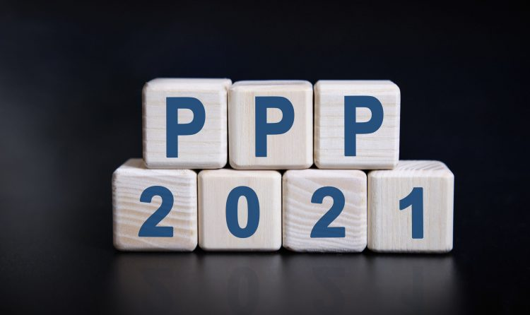 PPP 2021 text on wooden cubes on a black background with reflection.