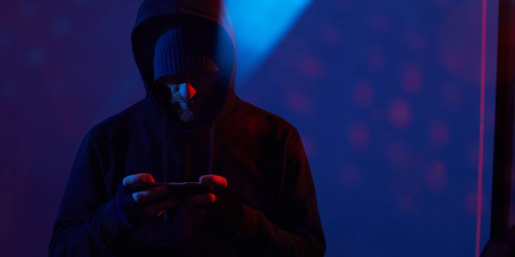 Image of computer hacker in black clothing standing and using his mobile phone in dark room